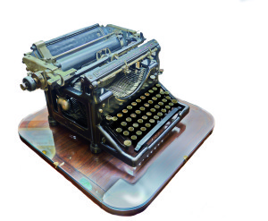An old manual typewriter on a wooden table - isolated on white